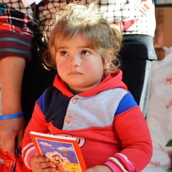아랍어로 된 ACN 어린이 성경을 들고있는 이라크 난민 소녀(출처=ACN 자료사진)