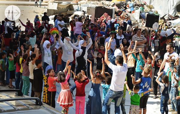 전쟁의 잔해 속에서 평화의 풍선을 날리는 어린이들. 출처=ACN자료사진