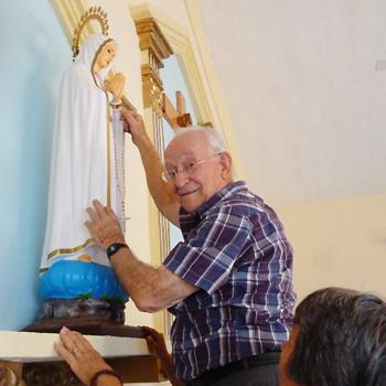 파티마의 성모상 손에 묵주를 거는 프란치스코 이투르베 신부님 (출처=ACN 자료사진)