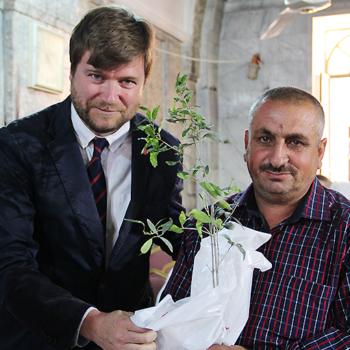 이라크 니네베 평원 마을 바르텔라에서 시리아 정교회 가정에게 올리브 나무를 전달하는 국제 ACN 사무총장 필립 오조레스 (출처=ACN 자료사진)