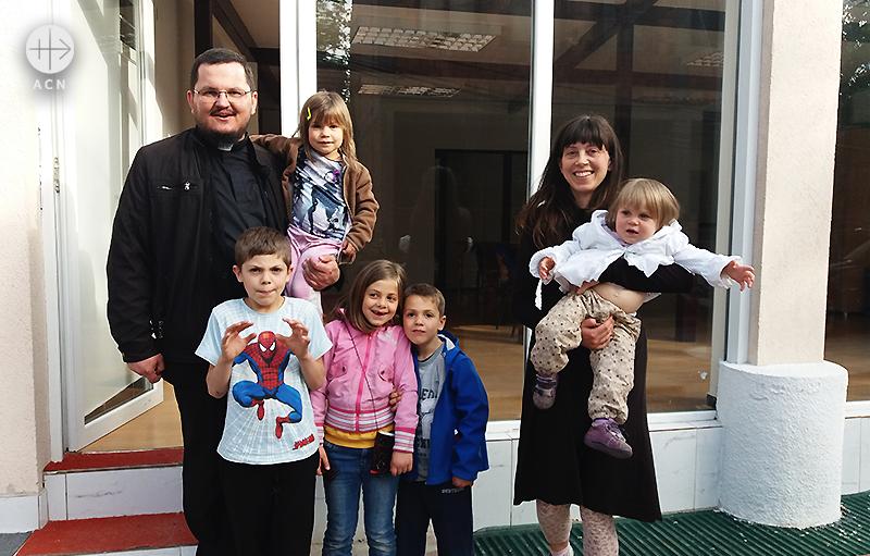 토마즈 박 신부님과 함께 안나와 그 자녀들, 쿠마노보의 성전 앞에서 (출처=ACN 자료사진)