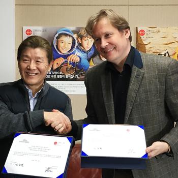 서울 마포구 소재 ACN 한국지부에서 트리니타스합창단 신호철 단장과 클라우자 지부장이 양해각서를 교환하고 있다.
