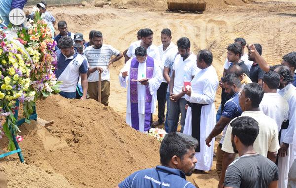 스리랑카 폭탄 테러 희생자들의 합동 장례 후 무덤 앞에기도하는 모습 (출처=ACN 자료사진)