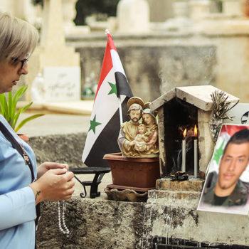 아들의 무덤 앞에서 묵주기도를 바치는 욜라 간두르 씨(출처=ACN 자료사진)