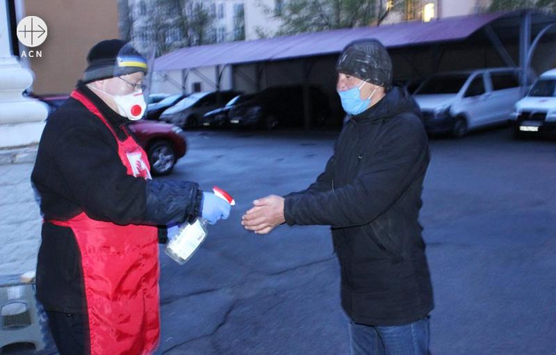 손 소독을 돕고 있는 우크라이나 카리타스의 세바스티안 장 수사
