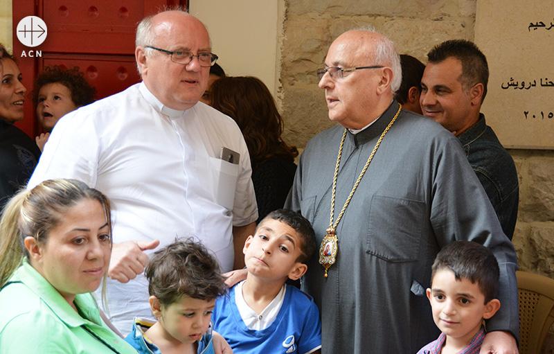 시리아 난민들과 함께 있는 레바논 자흘레의 이삼 존 다르위시 대주교와 할렘바 신부(출처=ACN 자료사진)
