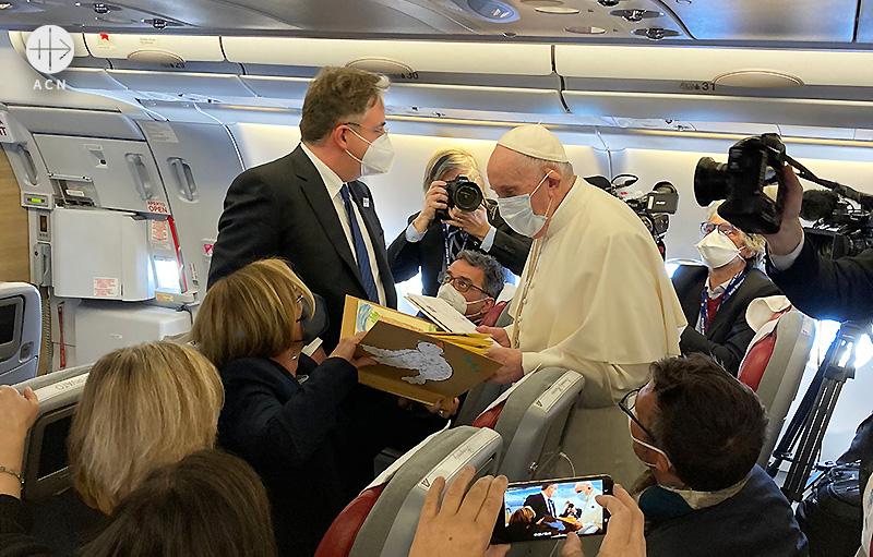 이라크행 비행기에서 프란치스코 교황에게 ACN의 지원으로 준비한 선물을 전달하는 스페인 출신 기자 (출처=ACN 자료사진)